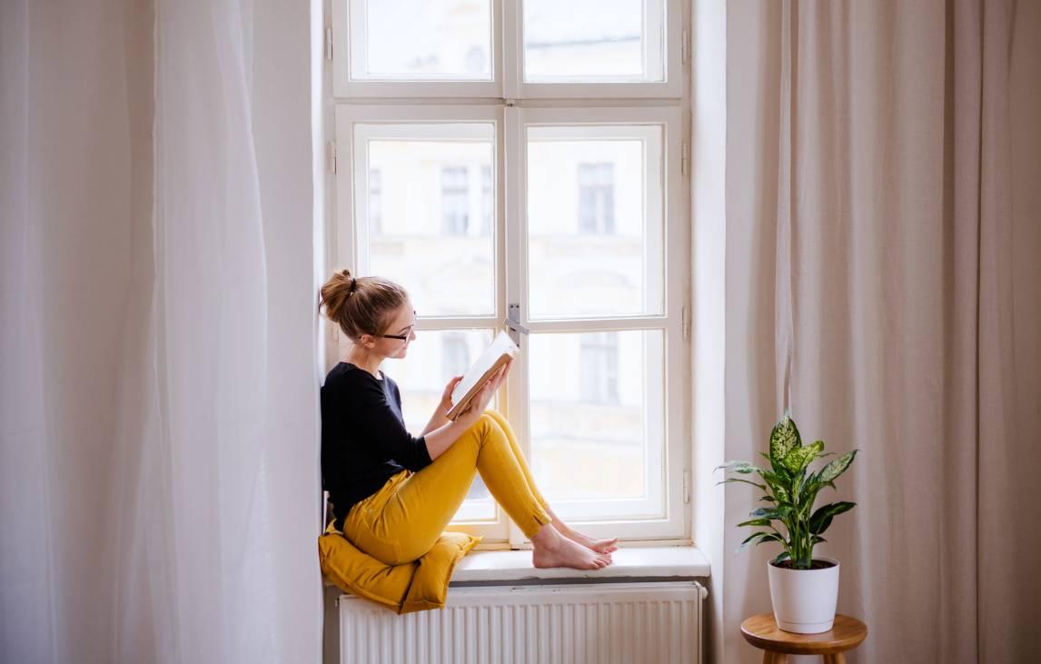 Femme se détend devant une fenêtre